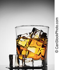 Glass of whiskey with ice melted