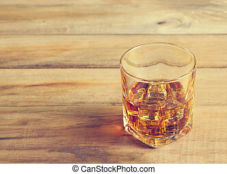 Glass of whiskey with ice on wooden background, Vintage color tone