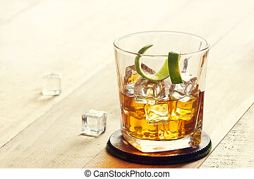 Glass of whiskey with ice on wooden background, warm color tone
