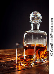 Glass of whisky besides decanter on a round table