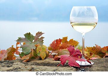 Glass of white *wine and autumn leaves against Geneva lake,...