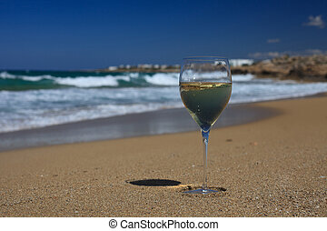 glass of white wine on the seashore against a blue sky.