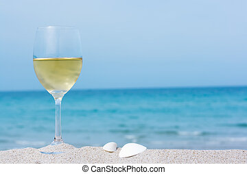 Glass of white wine on tropical beach