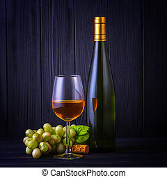 Glass of white wine with a bottle and grapes on back