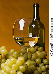 Glass of white wine with bottle and grapes.