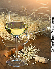 Glass of white wine with cork screw