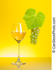 Glass of white wine with grape cluster