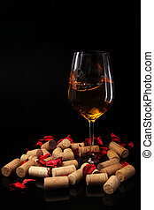 Glass of wine and corks on black background