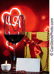 glass of wine and gift with a note on the table on a red background with hearts and a candle