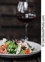Glass of wine and green salad with prosciutto and blue cheese on dark wooden background