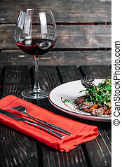 Glass of wine and salad with warm veal served with red napkin on dark wooden background