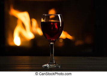 Glass of wine in front of fireplace