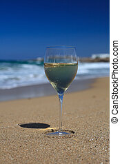 glass of wine on the sand on the beach against a blue sky