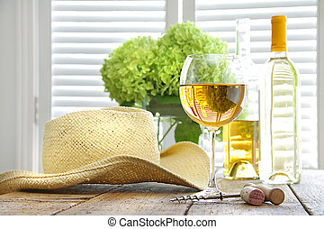 Glass of wine with straw hat on table