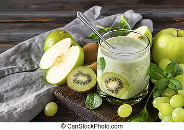 glass of yoghurt with fresh kiwi, green Apple, grapes and mint on a grey napkin