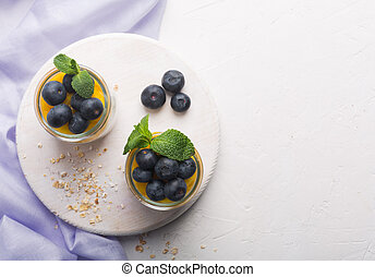 Glass of yogurt with blueberries and mango mousse on a white background