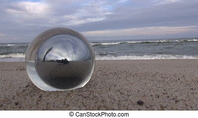 Glass orb by the sea - Glass orb with reflection of man by...