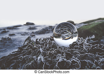 Glass orb on frozen leaves in the winter