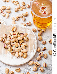 Glass pint of craft lager beer with pistachio nuts on stone kitchen table background. Beer and snack
