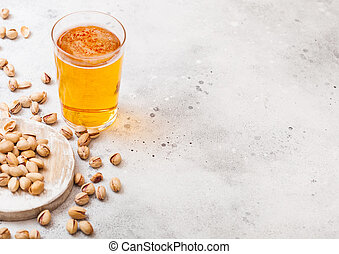 Glass pint of craft lager beer with pistachio nuts on stone kitchen table background. Beer and snack. Space for text