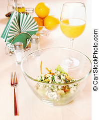 Glass plate with salad on the laid table