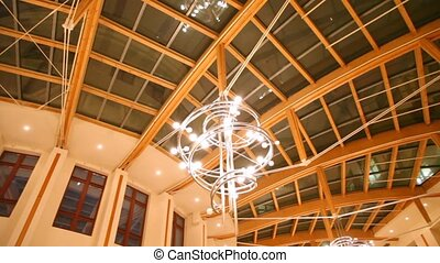 Glass roof of building with decorative lamps