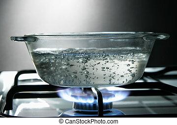 Glass saucepan on the gas stove close-up