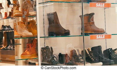 Glass showcase shoe store on which the inscription sale. Stylish autumn-winter shoes on the counter of the expensive storefront. Various fashion boots at discount