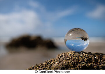 Glass sphere lying on the rock of a beach on a sunny