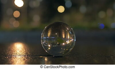 Glass sphere on the road in night city