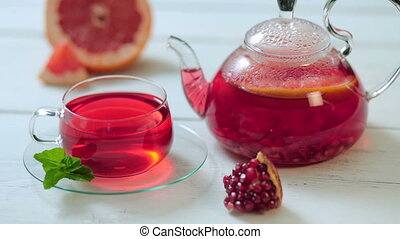 Glass teapot and cup of red tea with grape, pomegranate, mint on a white wooden table