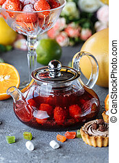 Glass teapot with fruit raspberry tea and mint on a blue background with fruits and decorations