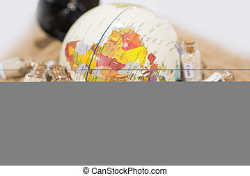 Glass test-tube with sand of different summer vacation countries. Located in sand with small globe.