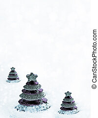 Glass toy Christmas tree in snow.