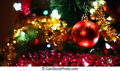 glass toy red ball hangs on Christmas tree among of blinking garlands