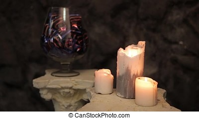 Glass vase with chocolates and candy and burning candles in...