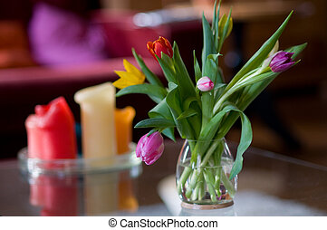 glass vase with colorful tulips in interior