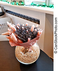 Glass vase with dry plants