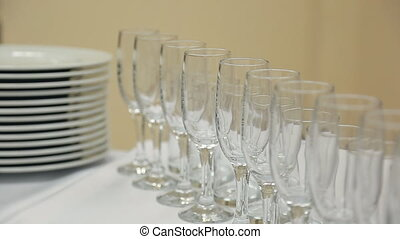 Glass wine glasses or champagne standing on table with a white cloth with ceramic plate.