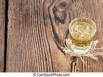 Glass with Apple Liqueur on dark vintage wooden background