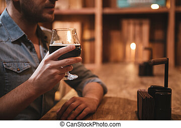 Glass with beer being held by a handsome nice man