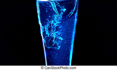 Glass with blue water on a black background