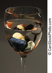 Glass with colored stones and water