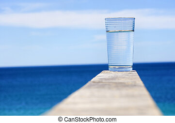 glass with crystal clear water against the blue ocean - as a...