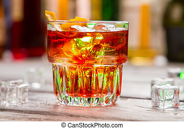 Glass with dark orange beverage.