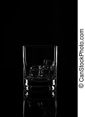 Glass with ice cubes, isolated on a black background
