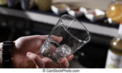 The bartender throws ice cubes in a glass