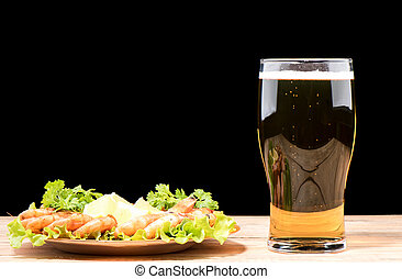 Glass with light beer on a wooden table.