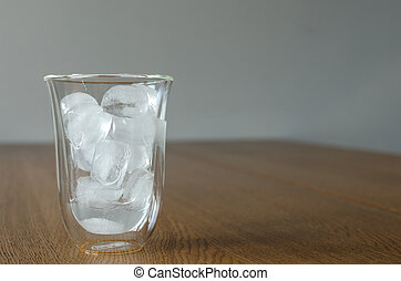 Glass with melting ice pieces on the wooden table. Ice is partially melted. Copyspace for text, background.