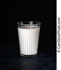 Glass with milk on a black background vertical shot